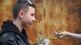 L'adolescente ricco del metraggio dà i soldi al prestito video d archivio