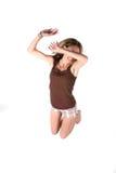 L'adolescente sautant avec son bras au-dessus de ses yeux photos libres de droits