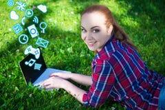 L'adolescente se trouvant sur l'herbe en parc et à l'aide de l'ordinateur portable avec diffèrent Photographie stock
