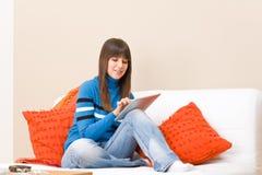 L'adolescente si distende con il calcolatore del ridurre in pani dello schermo di tocco Immagini Stock Libere da Diritti