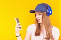 L'adolescente sorpreso utilizza le cuffie ed il telefono cellulare Fotografia Stock