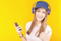 L'adolescente sorpreso utilizza le cuffie ed il telefono cellulare Immagini Stock