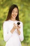 L'adolescente sorridente scrive il testo Fotografie Stock Libere da Diritti