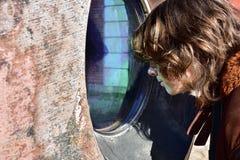 L'adolescente sta scrutando alla finestra blu-verde fotografie stock libere da diritti