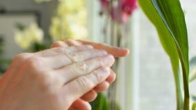 L'adolescente sta sfregando le mani che applicano la crema della protezione del sole al primo piano del dito del braccio video d archivio