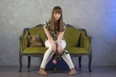L'adolescente triste s'assied sur le sofa vert sur le fond gris studio Image stock