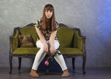 L'adolescente triste s'assied sur le sofa vert sur le fond gris studio Photographie stock