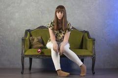 L'adolescente triste s'assied sur le sofa vert sur le fond gris studio Images stock