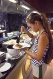 L'adolescente versa sullo sciroppo di cioccolato della cialda all'hotel fotografia stock libera da diritti