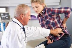 L'adolescente visualizza il dolore alla schiena dell'Office With del dottore fotografie stock libere da diritti