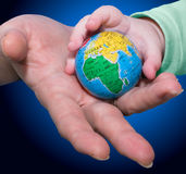 L'adulte donne le globe aux enfants Image libre de droits