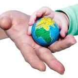 L'adulte donne le globe aux enfants Photographie stock libre de droits