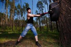 L'adulte en bonne santé fort a déchiré l'homme avec de grands muscles frappant le tyr de voiture image libre de droits