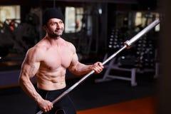 L'adulte en bonne santé fort a déchiré l'homme avec de grands muscles posant avec la barre image libre de droits