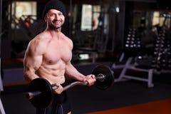 L'adulte en bonne santé fort a déchiré l'homme avec de grands muscles s'exerçant avec b photos stock
