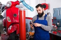 L'adulte est somme calculatrice pour réparer la moto Photo stock