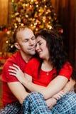 L'adulte a marié des couples dans des étreintes rouges de T-shirts et de pyjamas se reposant sur le plancher contre l'arbre de No Image stock
