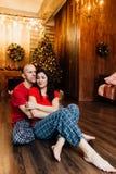 L'adulte a marié des couples dans des étreintes rouges de T-shirts et de pyjamas se reposant sur le plancher contre l'arbre de No Photographie stock
