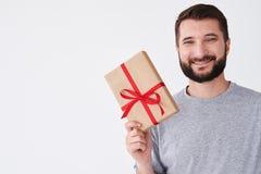 L'adulto berded l'uomo che sorride con il presente, considerante il suo giusto testo Fotografia Stock
