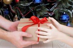 L'adulto dà un regalo al krop del bambino fotografia stock