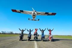 L'aereo bianco sta sorvolando cinque motociclisti che si siedono sui motocicli fotografie stock