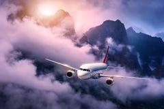 L'aereo bianco sta volando in nuvole porpora contro le alte montagne Fotografia Stock Libera da Diritti