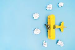 L'aereo d'annata e la carta del giocattolo del metallo giallo si appannano sul blu Fotografia Stock