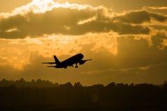 L'aereo della siluetta decolla nella mattina Fotografia Stock