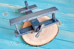 L'aereo di legno del giocattolo su un albero ha tagliato su un fondo di legno blu Fotografia Stock