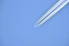 L'aereo di linea bianco trasporta i passeggeri mentre che tira le scie bianche in cielo blu Immagini Stock Libere da Diritti