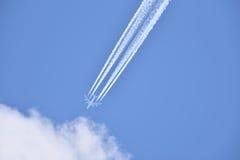 L'aereo di linea bianco trasporta i passeggeri mentre che tira le scie bianche in cielo nuvoloso blu Fotografie Stock