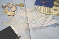 L'aereo, lo smartphone, il passaporto biometrico, i dollari, le monete e le carte di credito si trovano su una mappa fotografia stock