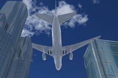 L'aereo vola sopra le costruzioni ad alta altitudine fotografie stock libere da diritti