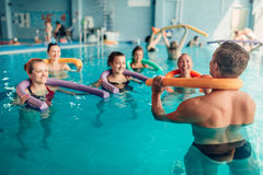 L'aerobica dell'acqua si esercita, donne con l'istruttore maschio Fotografie Stock