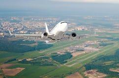 L'aeroplano è vista del livello di volo di salita alta nell'aria, contro lo sfondo dell'aeroporto della pista, città, campi, fore Immagini Stock Libere da Diritti