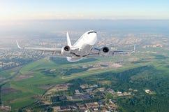 L'aeroplano è vista del livello di volo di salita alta nell'aria, contro l'orizzonte del cielo del fondo l'aeroporto della pista, Immagini Stock