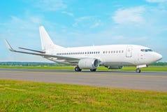 L'aeroplano bianco del passeggero guida la pista di rullaggio della pista all'aeroporto, contro un fondo di un cielo blu nella pr Fotografia Stock