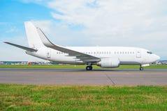 L'aeroplano bianco del passeggero guida la pista di rullaggio della pista all'aeroporto, contro un fondo di un cielo blu nella pr Immagini Stock