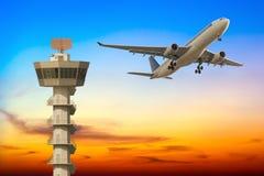 L'aeroplano commerciale decolla sopra la torre di controllo dell'aeroporto a sunse Fotografie Stock