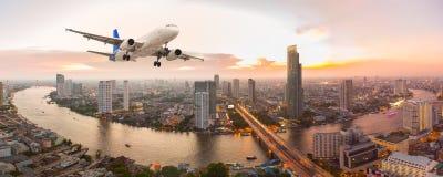 L'aeroplano decolla sopra la città di panorama al tramonto fotografia stock