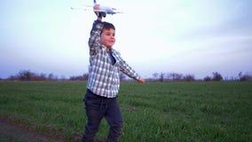 L'aeroplano del giocattolo in mani del ragazzino funziona all'aperto su fondo del campo e del cielo stock footage
