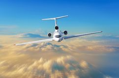 L'aeroplano del passeggero con tre motori sulla coda pilota l'alta velocità nel cielo sopra le nuvole ed il tramonto arancio, la  Fotografie Stock