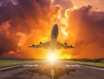 L'aeroplano della siluetta decolla dalla pista sul tramonto fotografia stock libera da diritti