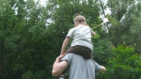 L'aeroplano di modello del lancio del figlio e del papà insieme all'aperto, sia uomo che ragazzo sta osservando allegramente l'ae stock footage