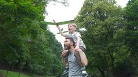 L'aeroplano di modello del lancio del figlio e del papà insieme all'aperto, sia uomo che ragazzo sta osservando allegramente l'ae archivi video