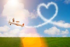 L'aeroplano di volo dell'uomo e fare forma del cuore Immagine Stock Libera da Diritti