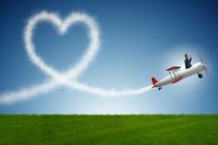 L'aeroplano di volo dell'uomo e fare forma del cuore Immagine Stock