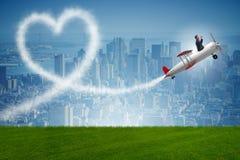 L'aeroplano di volo dell'uomo e fare forma del cuore Fotografie Stock