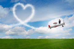 L'aeroplano di volo dell'uomo e fare forma del cuore Fotografia Stock