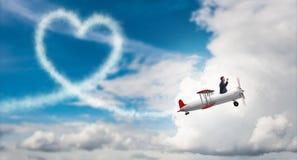 L'aeroplano di volo dell'uomo e fare forma del cuore Fotografie Stock Libere da Diritti